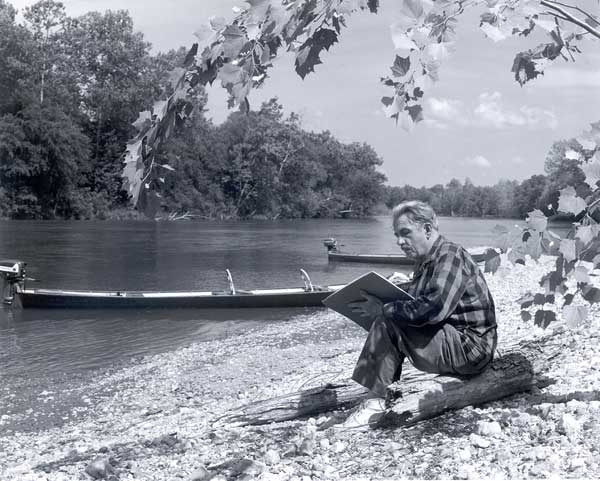 Benton sketching by a river.